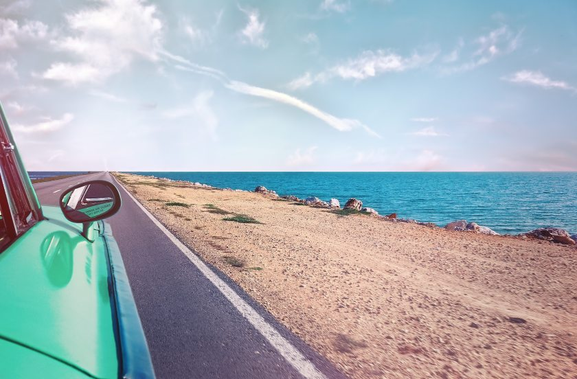 green-car-near-seashore-with-blue-ocean-1118448